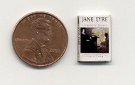 A miniature edition of JE, set beside a penny to show the scale of the book.